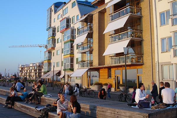 people sitting, walking and talking along a boardwalk