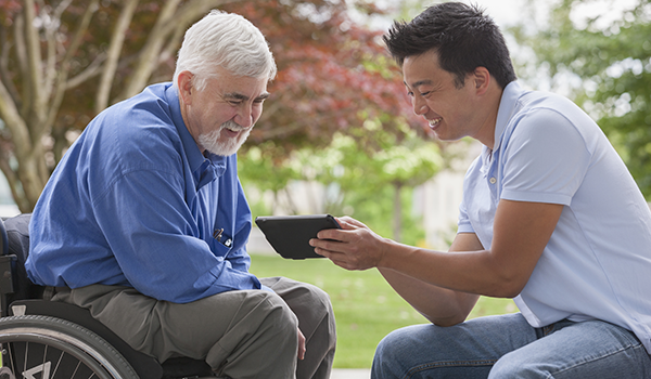 older man in wheelchair learning how to use an smart tablet