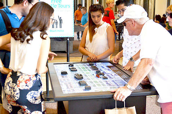 Group of visitors looking at the touch model at the national mall model located in Smithsonian Castle