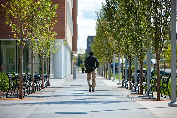 person walking along greiner hall sidewalk