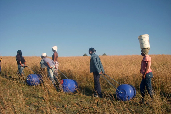 individuals pulling portable water carriers