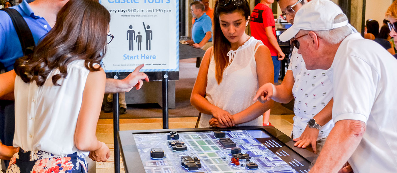 Group of visitors looking at the touch model at the smithsonian castle
