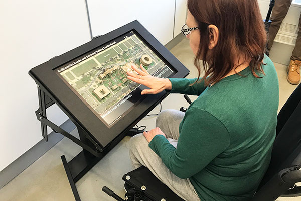 wheelchair user interacting with the smithsonian prototype touch model